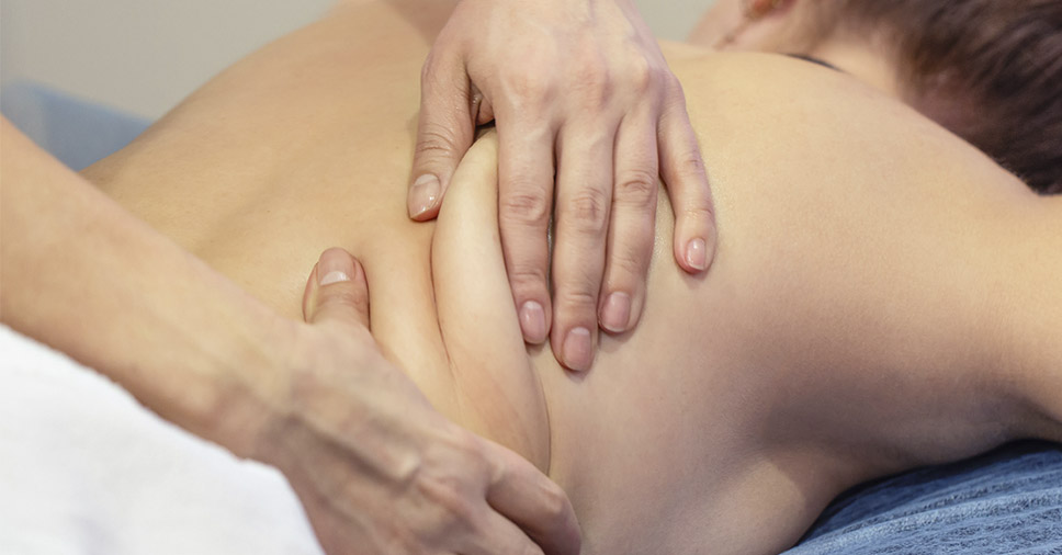 Mulher recebendo massagem feita por uma massoterapeuta